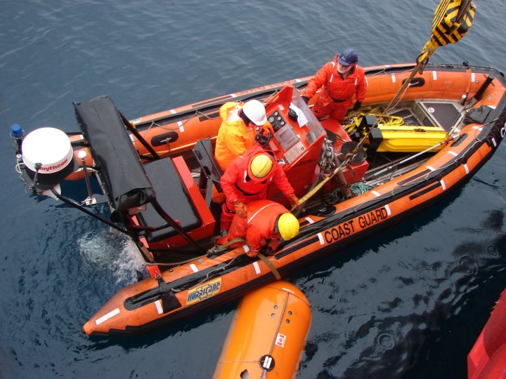 An orange inflatable boat, seen from above. Several figures in hardhats and orange jumpsuits are standing inside.