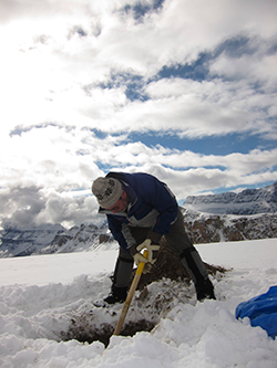 A man digs a hole in the snow, a mountain range in the distance behind him.