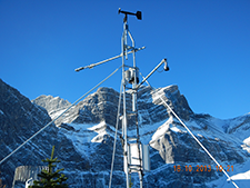 A weather station formed of narrow antennas is dwarfed by the snow-covered mountains behind it.