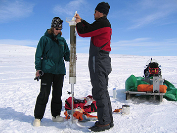 Two researchers use a tool to examine sediment beneath a frozen lake so they can get information about environmental changes.
