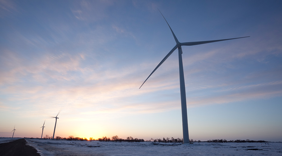 A lone wind turbine cuts through the pastel sky in the middle of a snowy field.