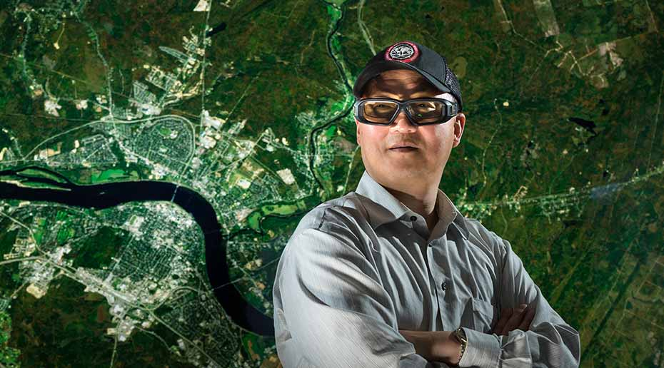 A man wearing 3D glasses stands in front of a satellite map.