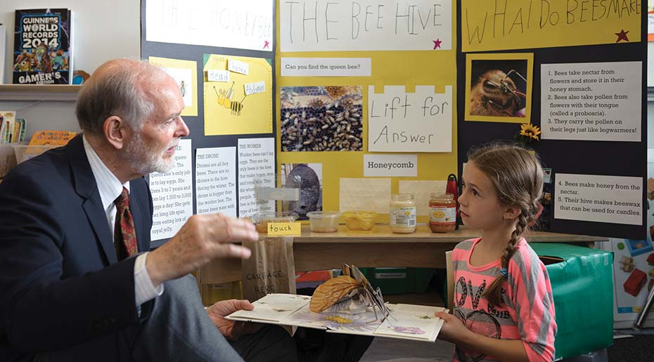 An older man talks to a young girl seated in front of a yellow and black poster board project on bees.