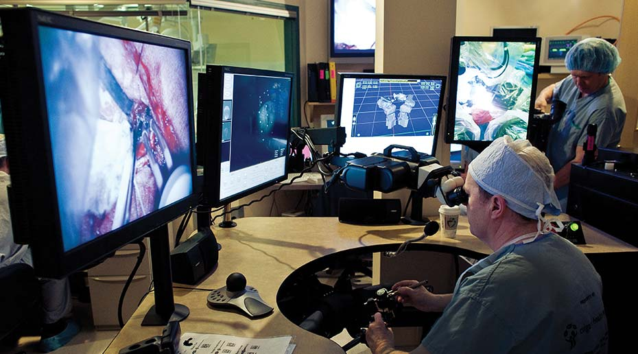 A man performs neurosurgery by looking through an eye piece and using hand controls to guide a robot. He is surrounded by multiple computer screens with live camera feeds.