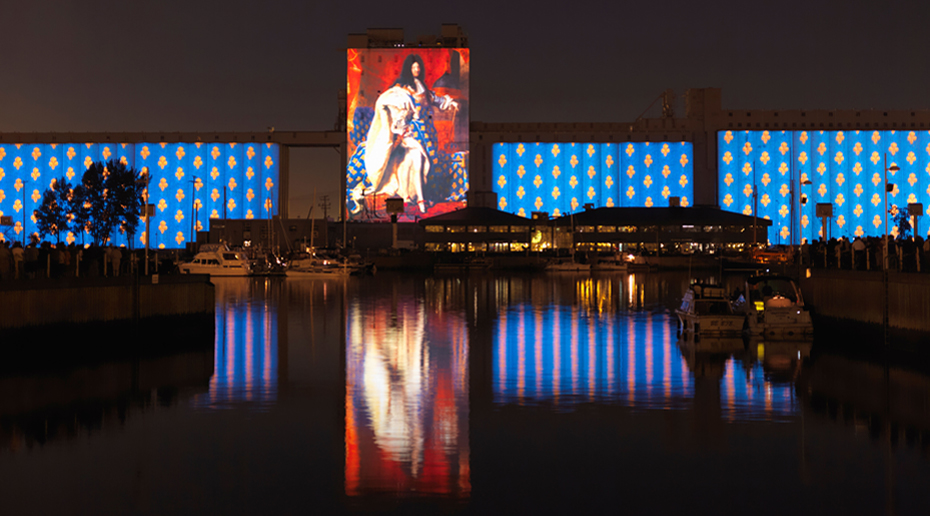 An image of King Louis the fourteenth is projected onto buildings and reflected in a body of water in the foreground.