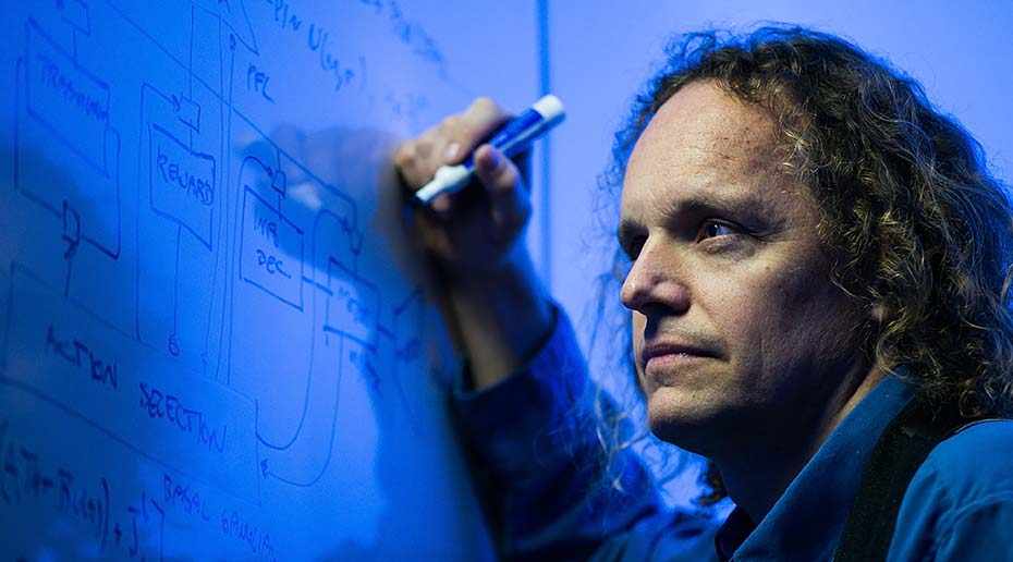 A man focuses intently as he writes equations on a large whiteboard.