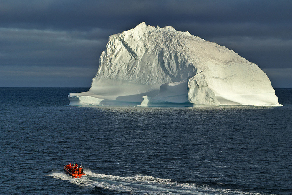 A small orange Zodiak boat heads towards a large white iceberg