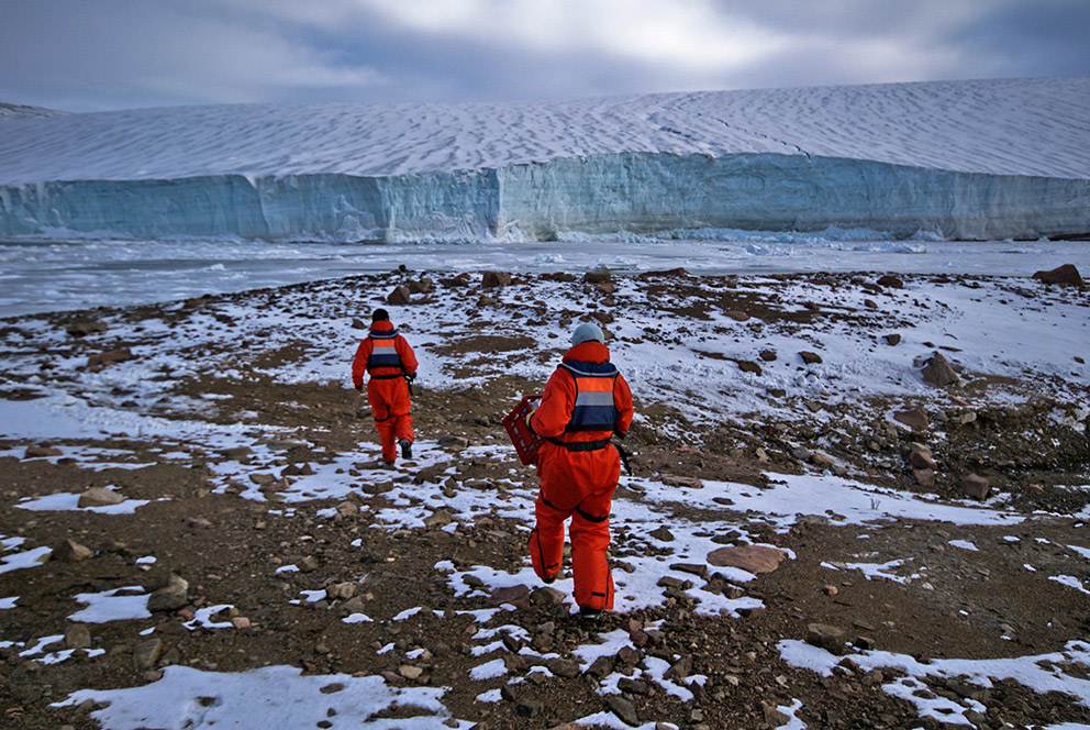 Two people in orange body suits walk across rocky terrain covered in patches of snow towards a massive glacier