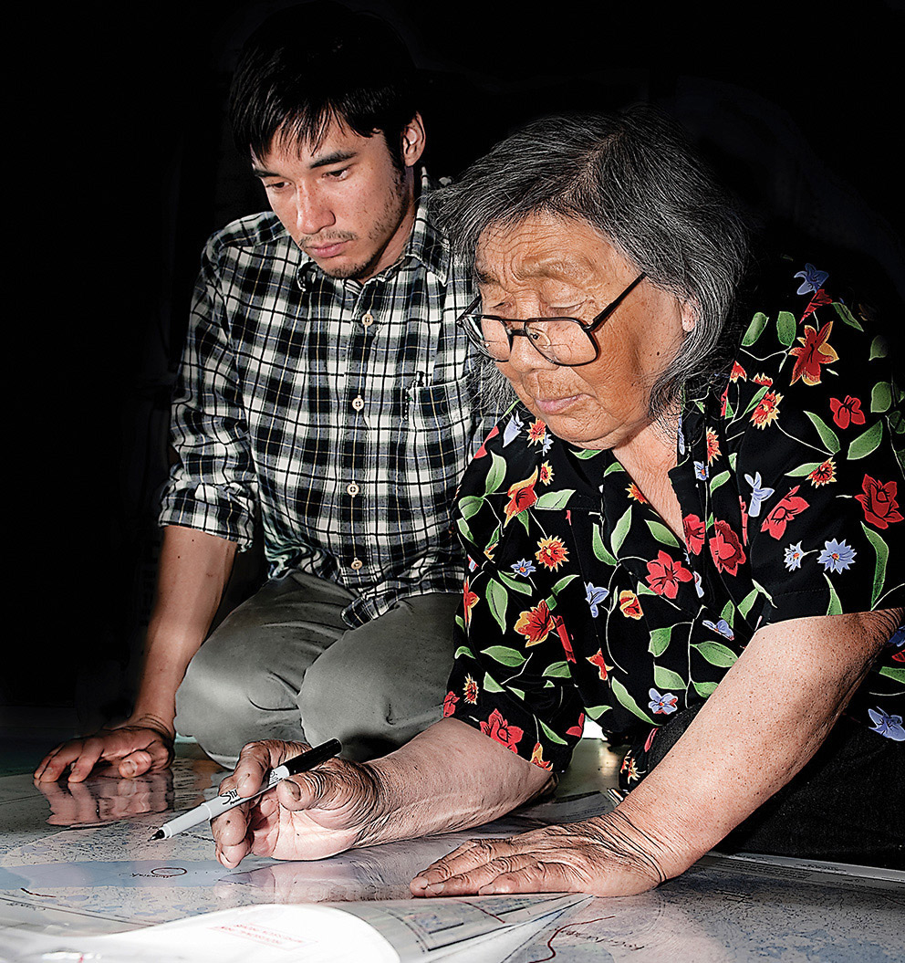 Two people bend over a large map on a light table
