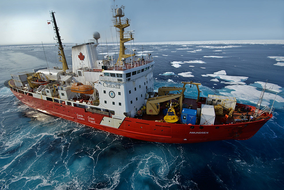 A large red and white icebreaker sails through Arctic waters.