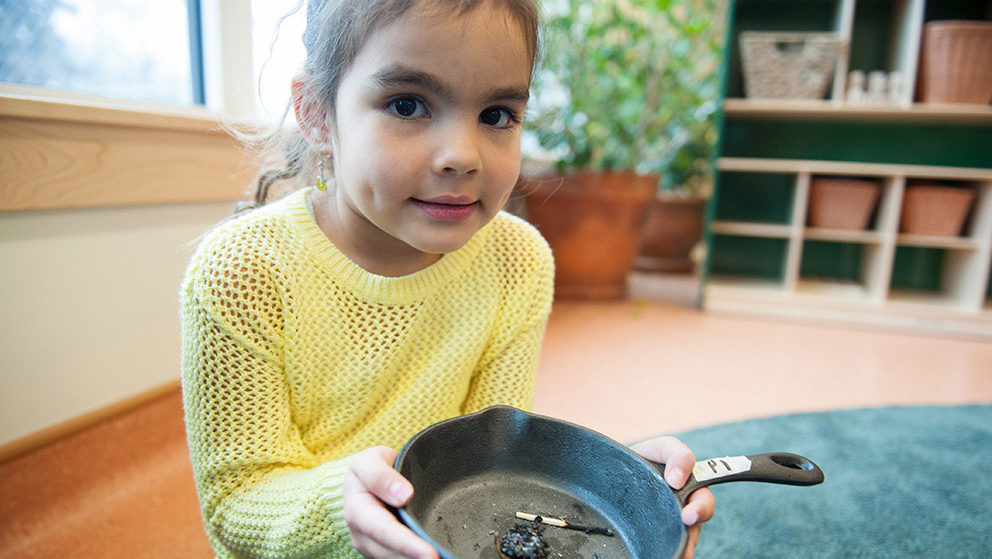 A young girl in a yellow sweater holds out a cast-iron smudging pan with burned herbs in it.