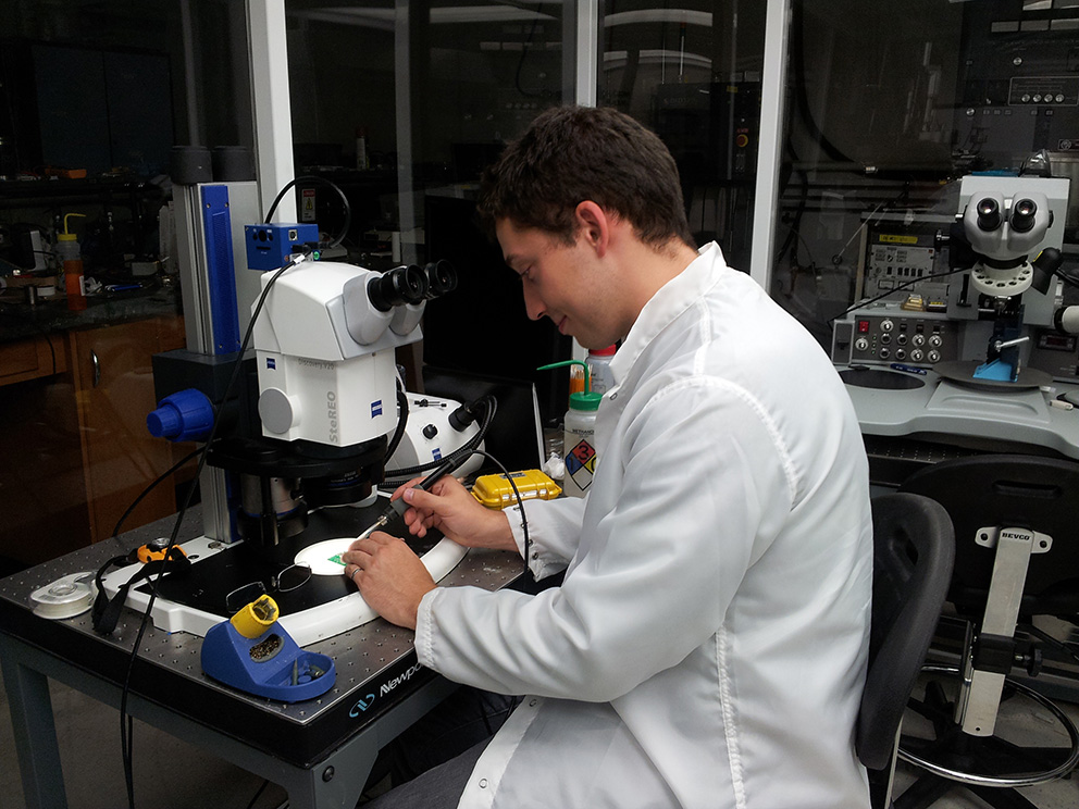 A young man in a white lab coat looks down at a sample on the stage of a microscope, with other lab equipment visible in the background.