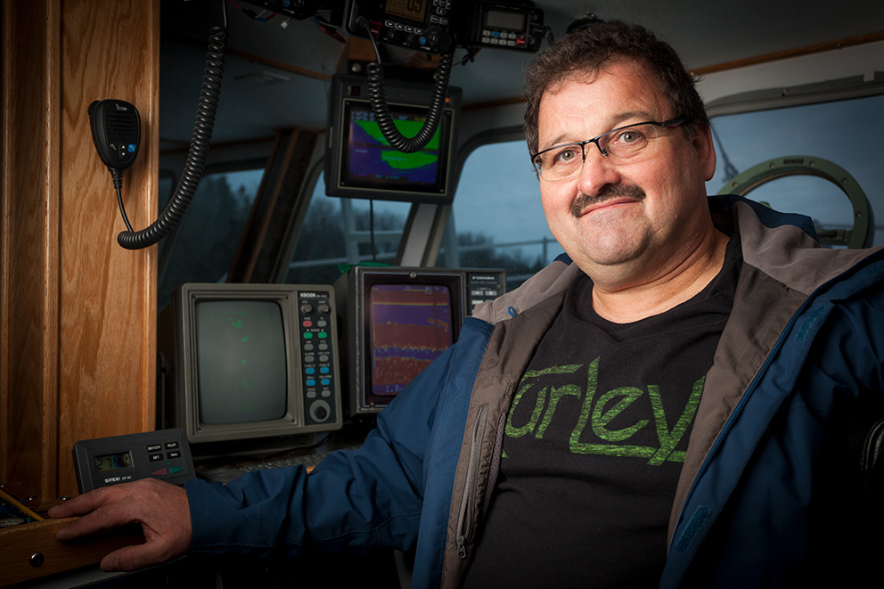 A mustachioed man with glasses stands in a ship cabin in front of several navigation screens and controls.