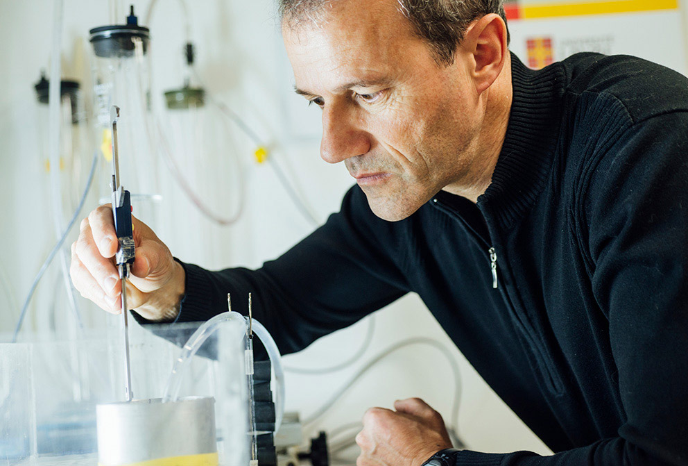 A man works with glassware and tubing in a lab.