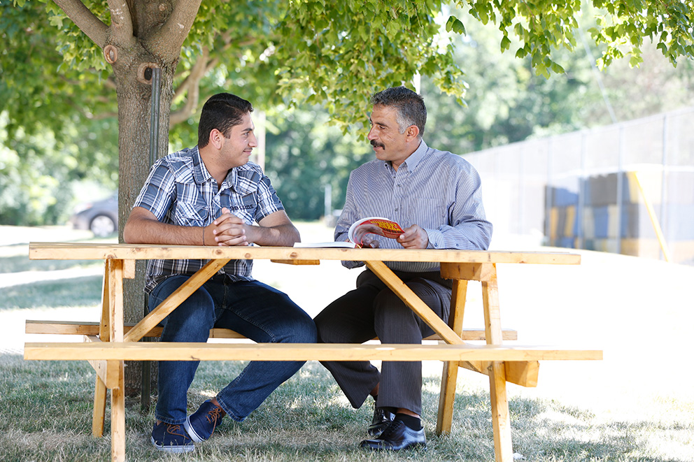 A teenage son and his father sit at a picnic table reading a book.