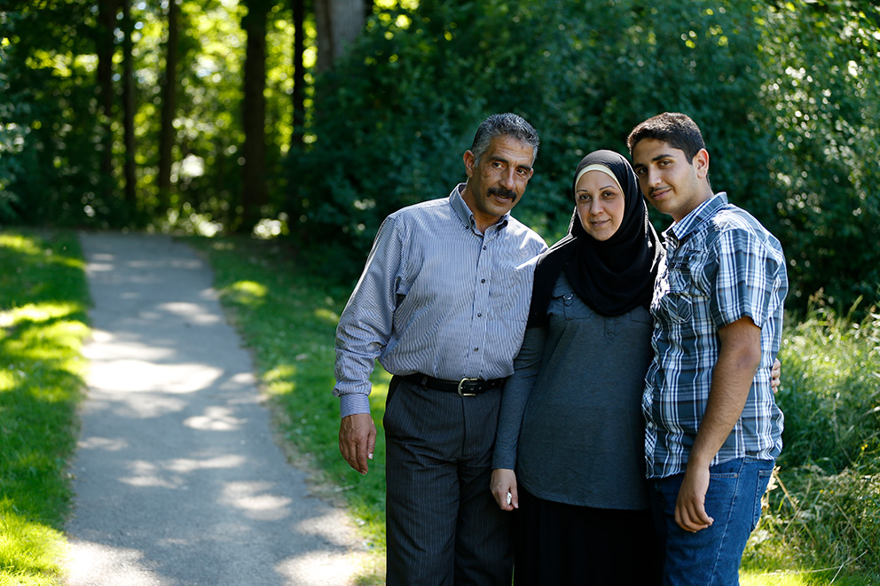 A husband and wife and their grown son stand by a path leading into a forest.