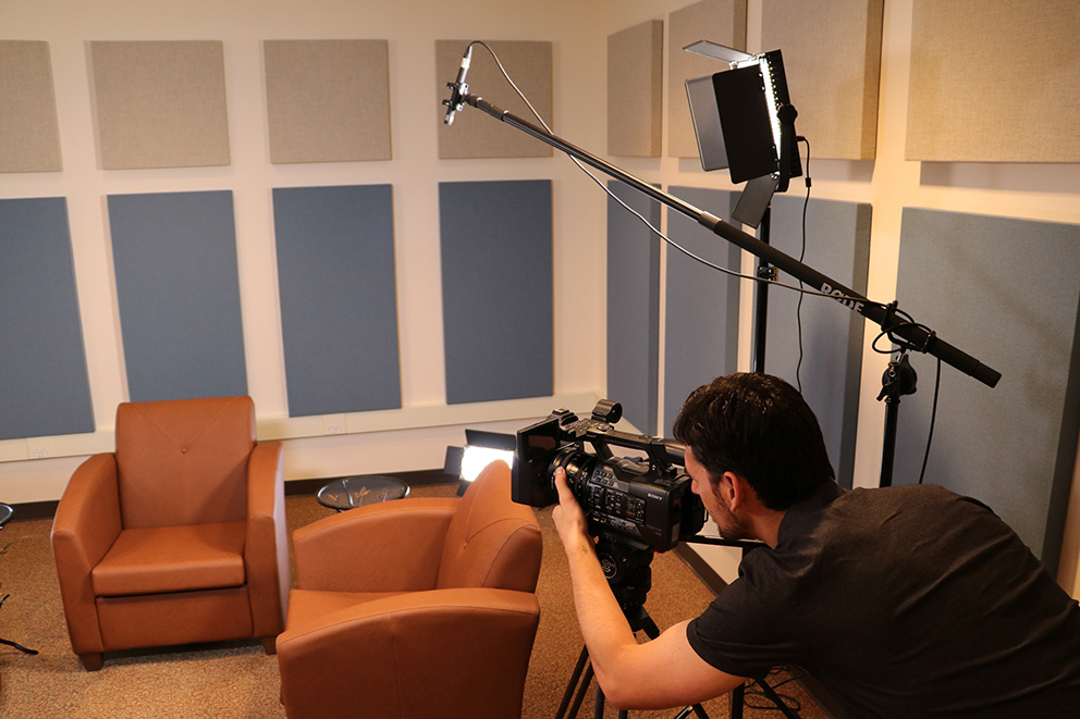 A man uses lighting and camera equipment to film a room with two orange chairs.