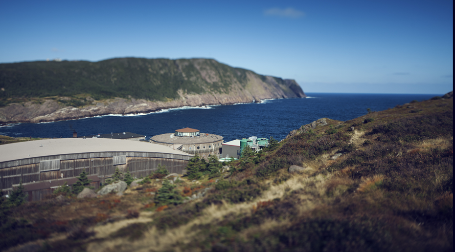 A rocky coast line with a navy blue sea and clear blue sky, a circular wooden building in the middleground.