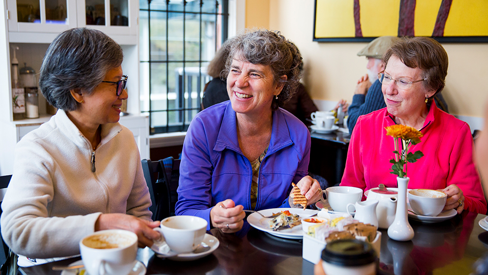 Three women sit in a café talking and laughing over lunch.