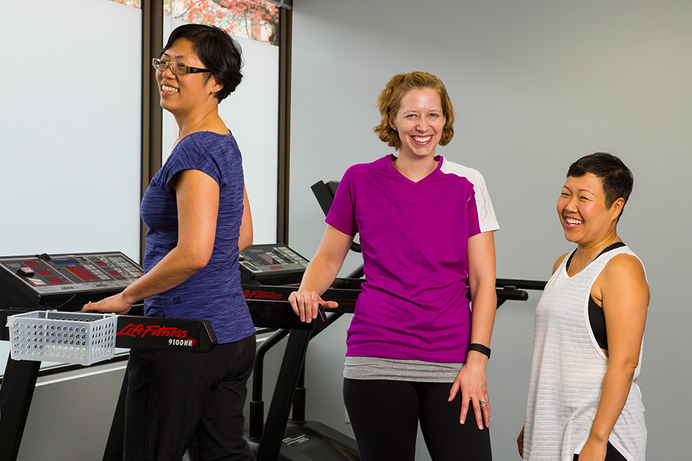 A woman uses a treadmill while two other women stand chatting beside her.