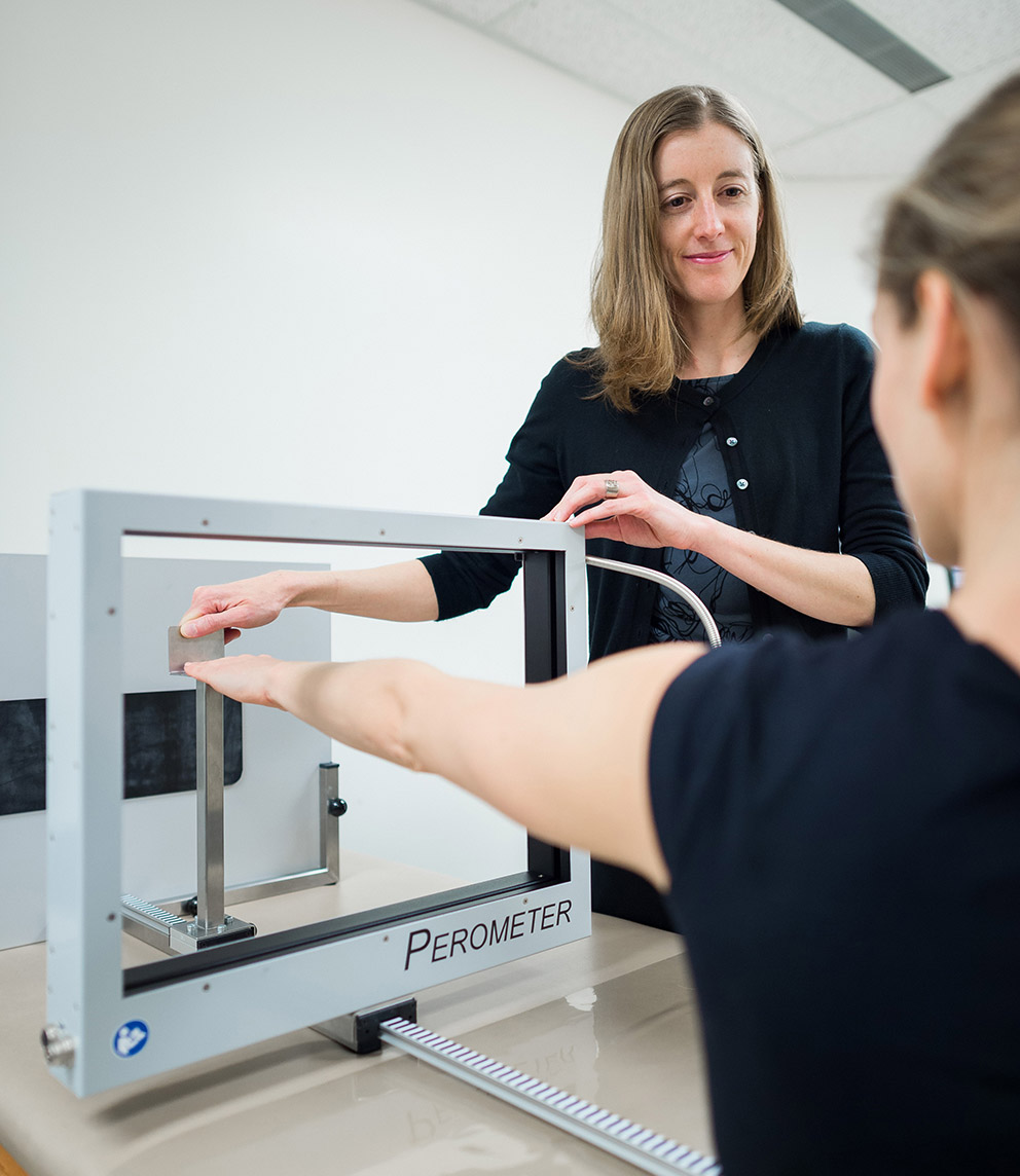 A young woman puts her arm through a square frame that is part of a machine so a female researcher can examine it.