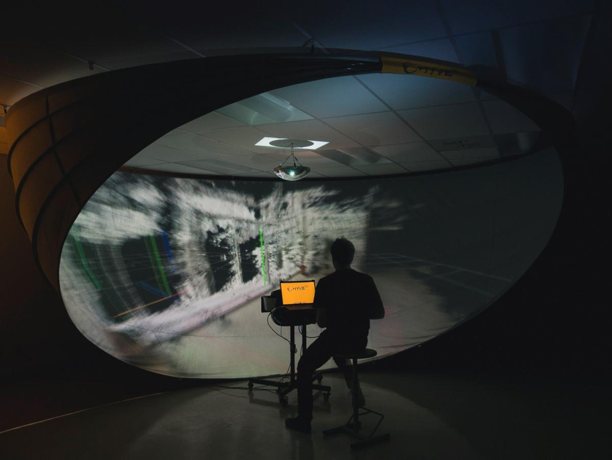 A circular screen surrounds a person, viewed from behind, looking at a laptop screen.