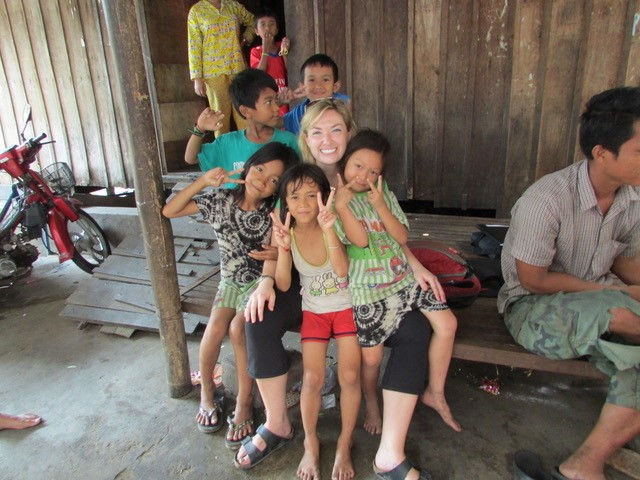 Researcher Kyly Whitfield surrounded by Cambodian children